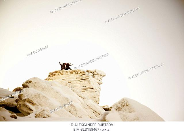 Caucasian hikers on snowy mountaintop