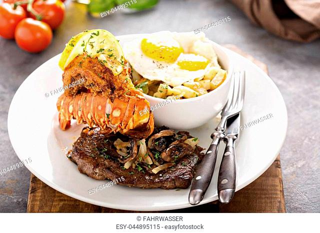 Southern surf and turf, steak and fried lobster tail with potatoes and eggs