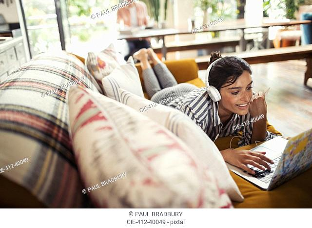 Smiling woman with headphones using laptop on sofa
