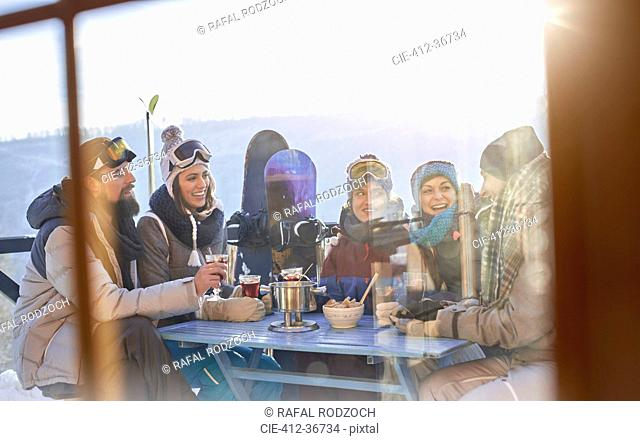 Snowboarder friends drinking and eating at balcony table apres-ski