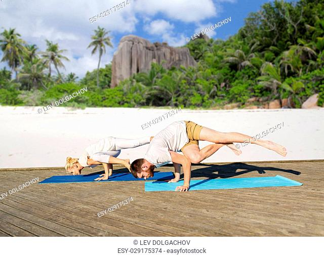 fitness, sport and healthy lifestyle concept - people making yoga exercises outdoors over exotic tropical beach background