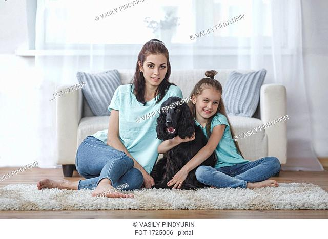 Portrait of mother and daughter with dog sitting on rug at home