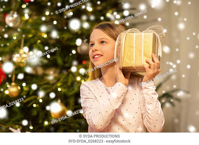 smiling girl with christmas gift at home