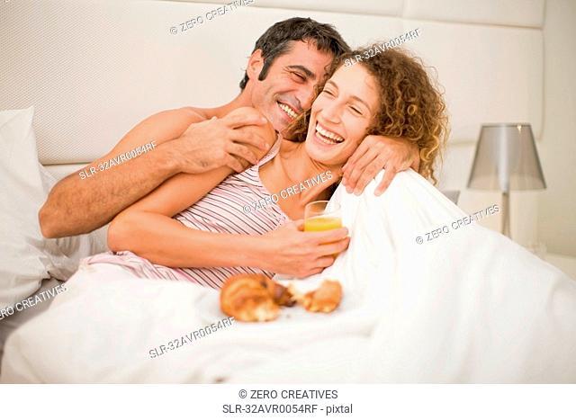 Smiling couple having breakfast in bed