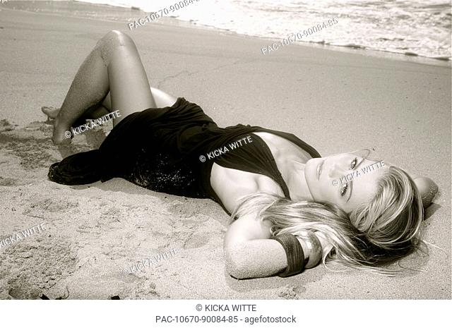 Hawaii, Kauai, Kealia, Beautiful fashion model on beach wearing a dress, black and white