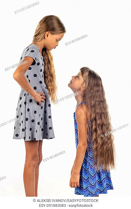 Two girls of different stature, one stood on a chair and became even taller