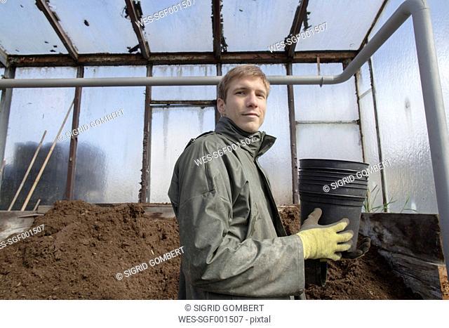 Young gardener at work, filling mother soil