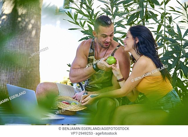 young muscular man giving girlfriend an healthy apple, while sitting in nature with modern technology devices. Greek ethnicity