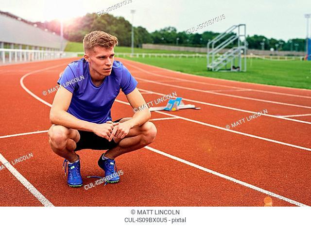 Runner resting on running track