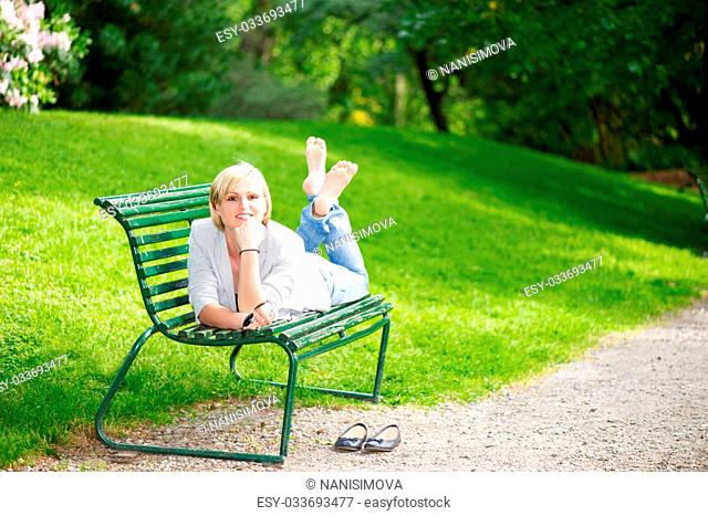 Young woman laying on bench in park and smiling