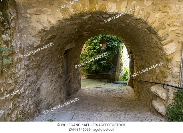 Village scene with an archway in Menerbes, a small village on a hill between Avignon and Apt, in the Luberon, Provence-Alpes-Cote d Azur region in southern...