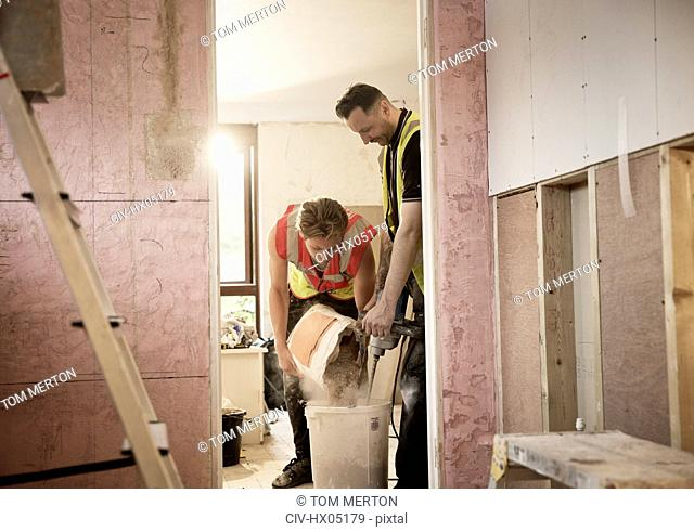 Construction workers mixing plaster in house