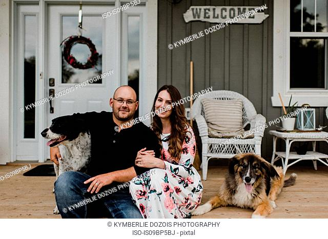 Couple and their two dogs sitting on porch