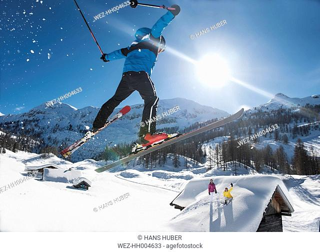 Austria, Salzburg, Young man ski jumping in mountains