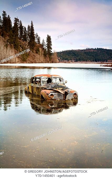 An old antique car sits swamped in a flooded pond