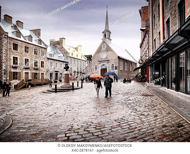 Rainy day view of Notre Dame des Victoires Roman Catholic Church and statue of Louis XIV in Place Royale. Royal Square with boutiques