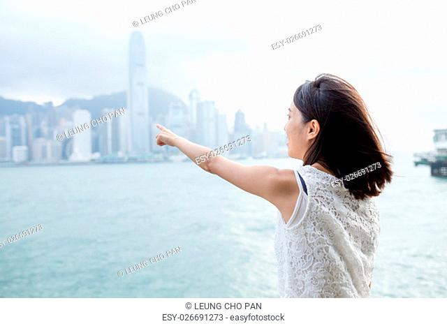 Woman finger point to the Hong Kong Island
