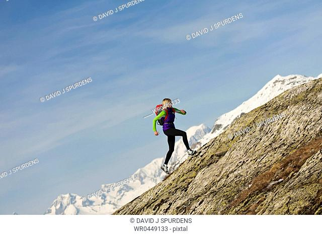 A woman jogging in high mountains runs up a steep peak