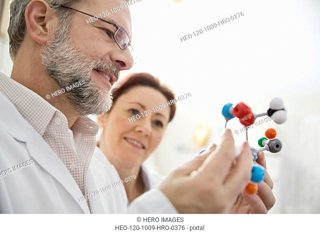 Mature doctors analyzing molecular structure together