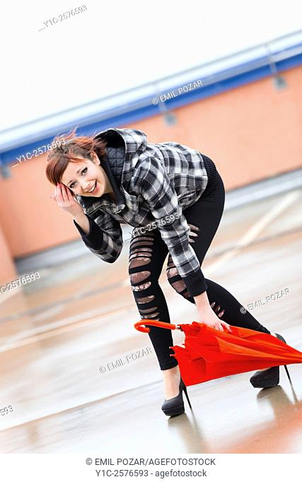 Laughing teenager girl is picking up Red umbrella