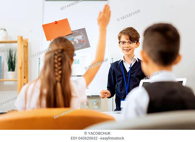 New teacher. Excited nice boy in glasses asking other children while standing in a class