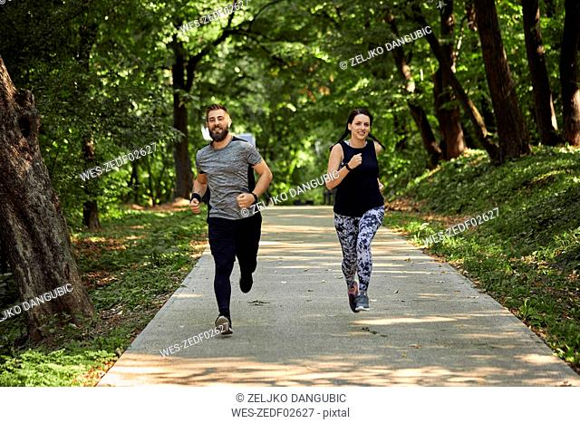 Sporty couple running on forest path