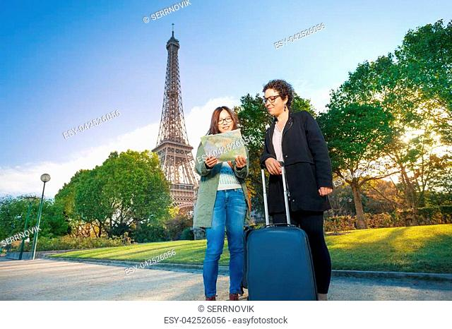 Two happy female travelers with their trolley case, reading map against the Eiffel Tower in Paris