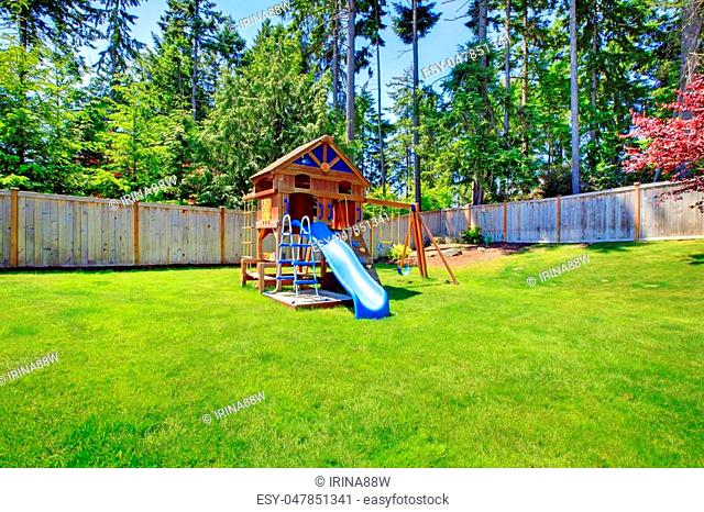 Play kids ground area with chute in fenced backyard. House exterior