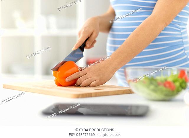 pregnant woman cooking vegetable salad at home