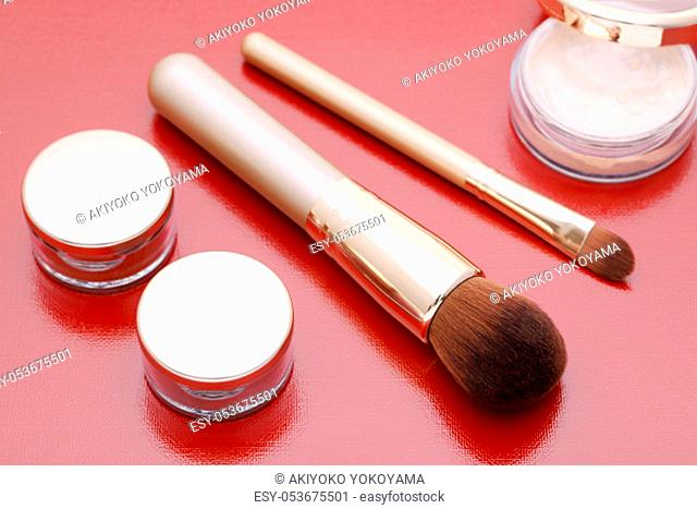 closeup of make up powder and brush on red background