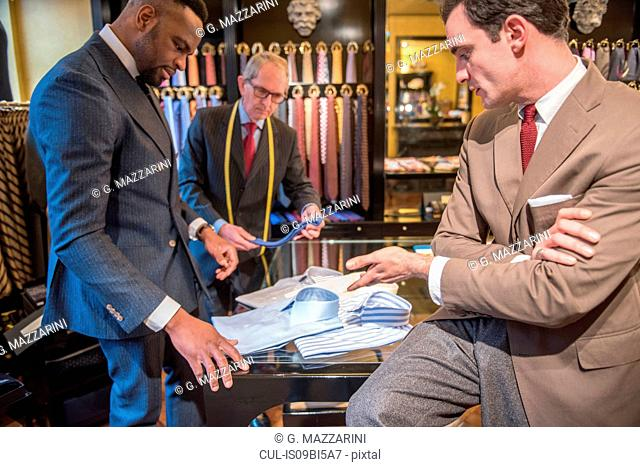 Tailor and customer looking at shirts in tailors shop