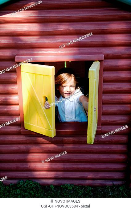 Smiling Young Boy Looking out Window of Plastic Log Cabin