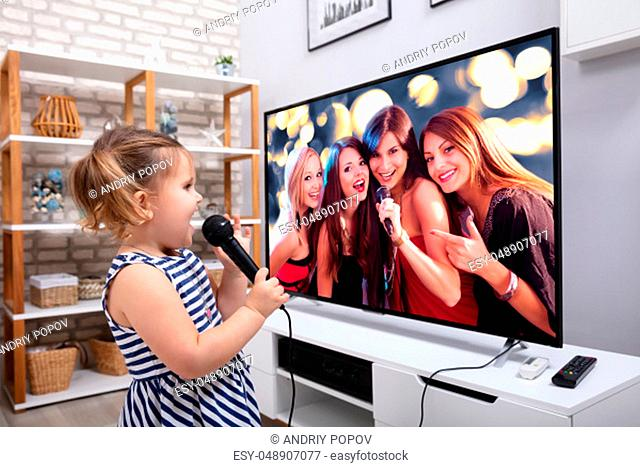 Close-up Of A Happy Girl Singing Song With Microphone In Front Of Television At Home