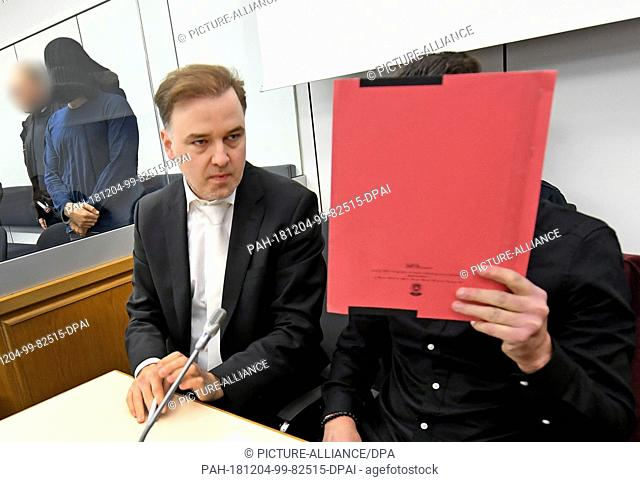 04 December 2018, Lower Saxony, Celle: A witness for the prosecution covers his face in a courtroom of the Higher Regional Court next to his defender Burkhard...