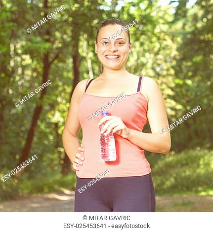 Fitness Smiling Healthy Young Woman with bottle of water outdoor