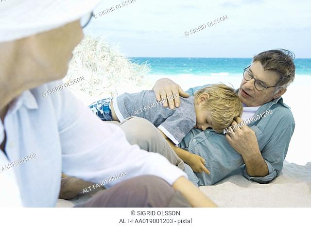 Family on beach, boy resting on grandfather