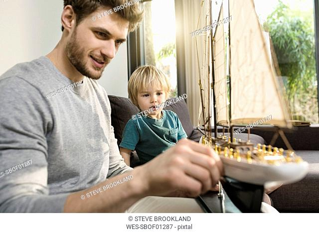 Father and son looking at toy model ship on couch at home