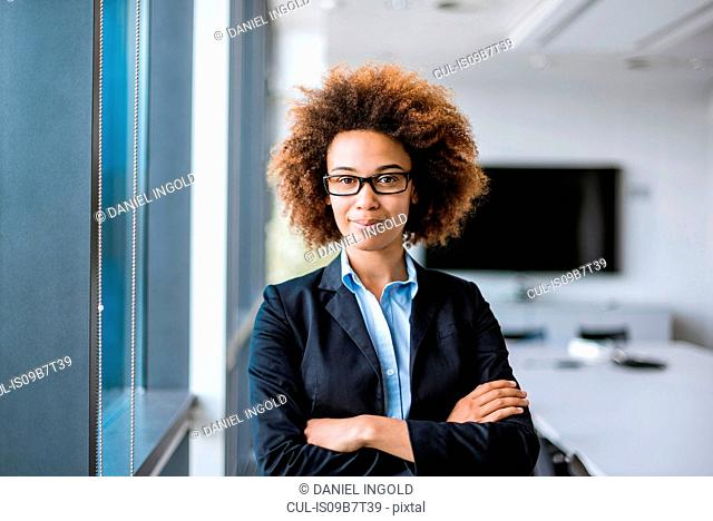 Portrait of confident young businesswoman with arms folded in boardroom