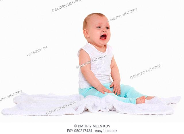 Little unhappy baby is sitting and crying on a plaid on white background. Eight months