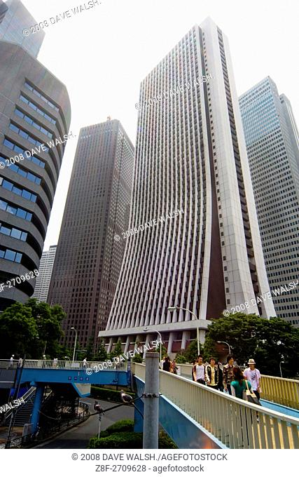 The 200-metre high Sompo Japan Head Office in Shinjuku's skyscraper district, with pedestrians crossing a bridge and two pigeons keeping watch