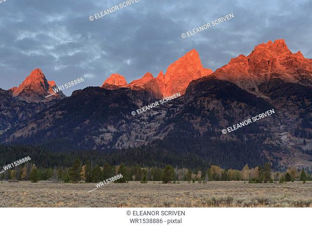 Cathedral Group of the Teton Range lit by intense dawn light in autumn (fall), Grand Teton National Park, Wyoming, United States of America, North America