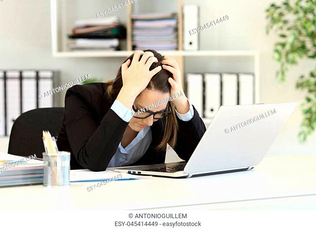 Sad office worker complaining after bankruptcy sitting in a desktop at workplace