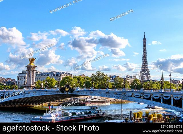 France. Sunny summer day in Paris. Pleasure boat under the bridge of Alexander III over the river Seine. Eiffel Tower