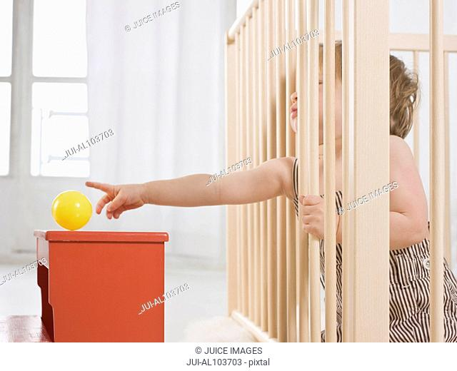 A young child trying to reach a yellow ball through some wooden bars
