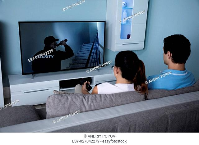 Rear View Of Couple Watching Film On Television In Living Room At Home