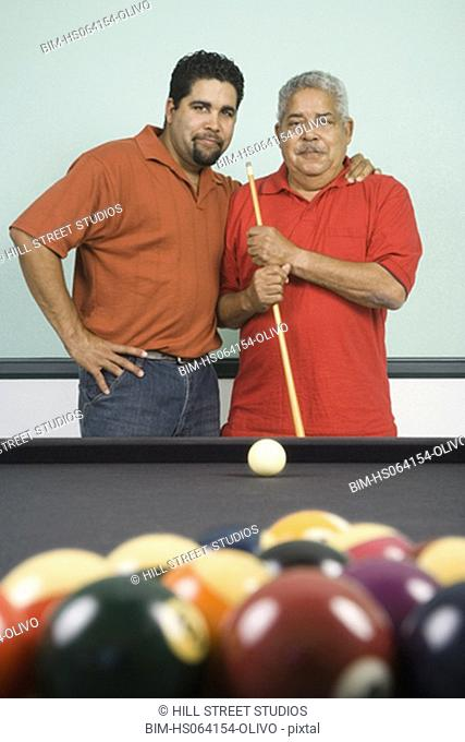 Hispanic father and adult son playing pool