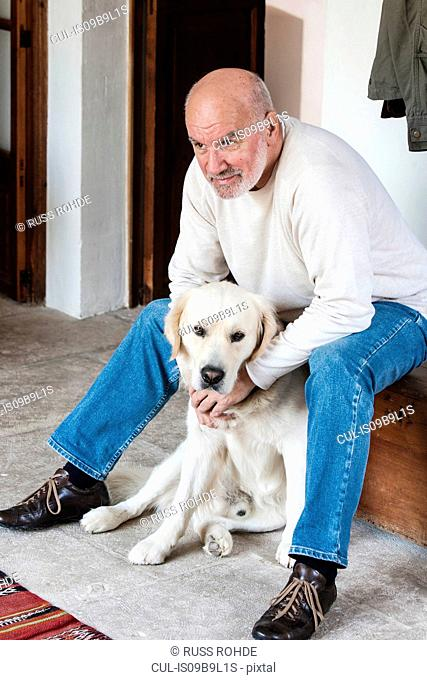 Portrait of senior man at home with pet dog