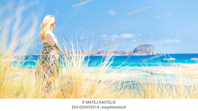 Relaxed woman wrapped in colorful scarf, enjoying sun, freedom and life at beautiful Balos beach in Greece. Concept of holidays, vacations, freedom