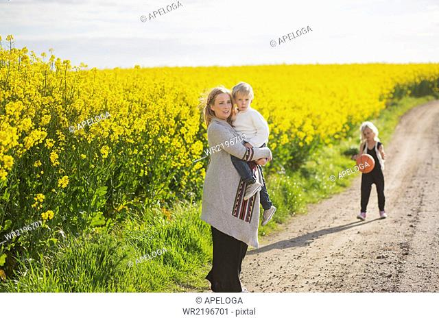 Woman carrying son while girl playing with basketball at rapeseed field