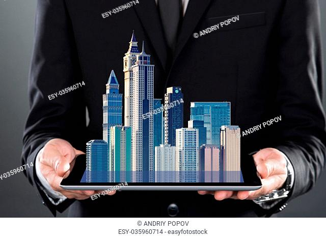 Midsection of businessman holding digital tablet over gray background